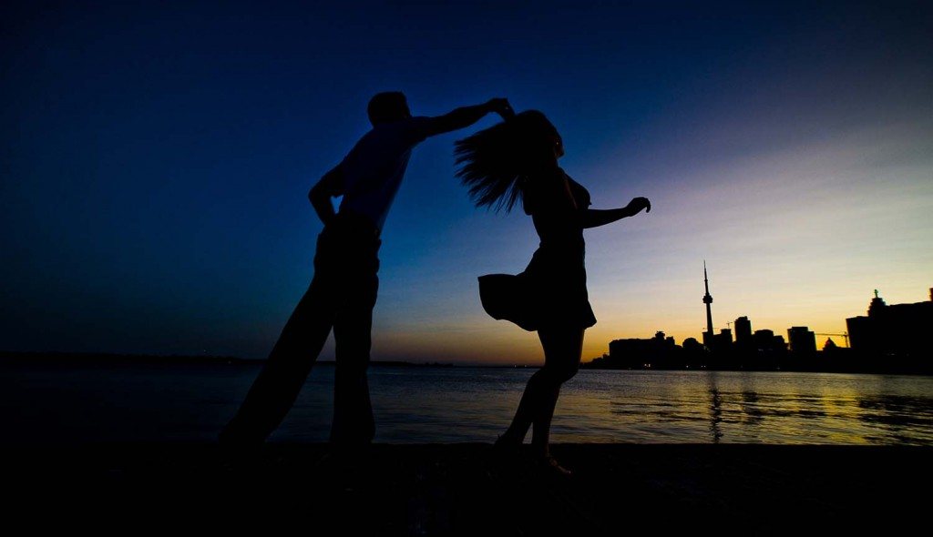 Toronto skyline with couple dancing at sunset.