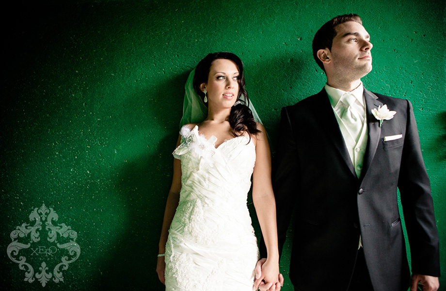 bride and groom in front of green wall